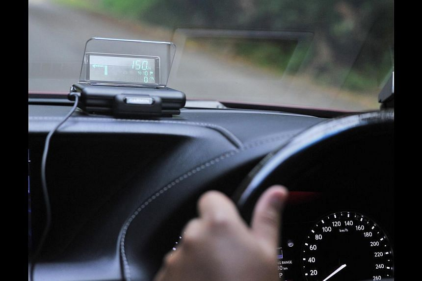 The Garmin Head-Up Display (above) is user-friendly, projecting navigation instructions on the windscreen, while the Marbella uNav gives clear audio and visual instructions. -- PHOTO: LIM YAOHUI FOR THE STRAITS TIMES