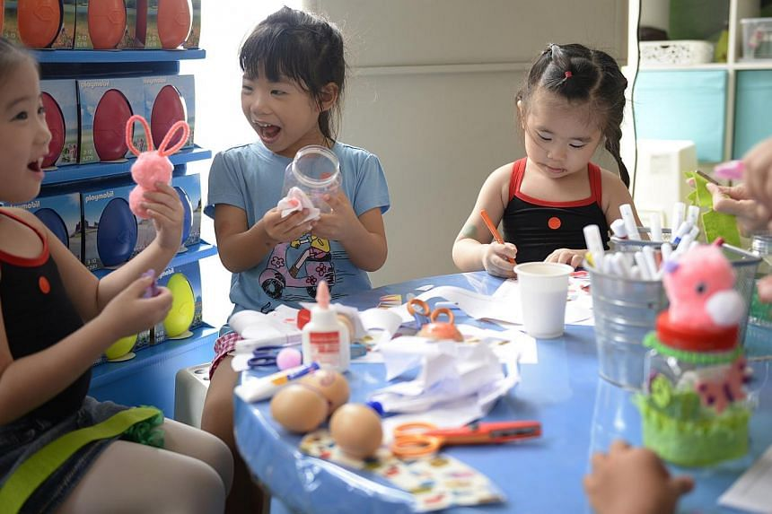 (From left) Natalie Tan, five, Joey Ong, six, and Kimberly Tan, three, decorating Easter eggs and making bunny bottles at the Sentosa Easter festival celebrations.