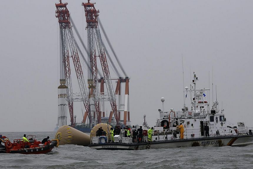Rescue workers operate near floats where the capsized passenger ship Sewol sank on April 19, 2014. -- PHOTO: REUTERS