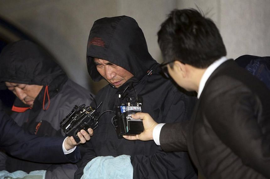 Journalists ask Lee Joon-seok (centre), captain of South Korean ferry Sewol which sank at sea off Jindo, questions as Lee walks out of court after an investigation in Mokpo April 18, 2014. -- PHOTO: REUTERS