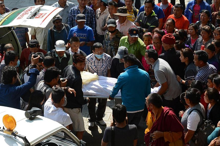 Nepalese relatives and volunteers shift the body of a Mount Everest avalanche victim after arrival at the Sherpa Monastery in Kathmandu, on April 19, 2014. Rescuers recovered the body of one mountain guide on Saturday after an ice avalanche swept the