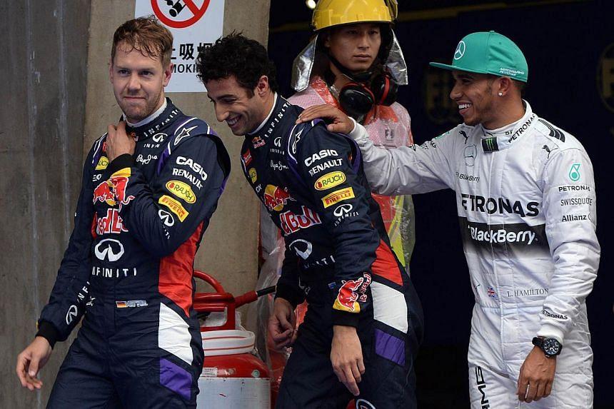 Mercedes AMG Petronas driver Lewis Hamilton of Britain (right) celebrates after qualifying in pole position beside second fastest Infiniti Red Bull driver Daniel Ricciardo of Australia (centre) and third fastest Infiniti Red Bull driver Sebastian Vet