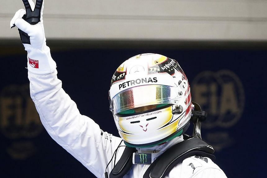 Mercedes Formula One driver Lewis Hamilton of Britain gestures as he celebrates taking pole position after the qualifying session for the Chinese F1 Grand Prix at the Shanghai International circuit, on April 19, 2014. -- PHOTO: REUTERS