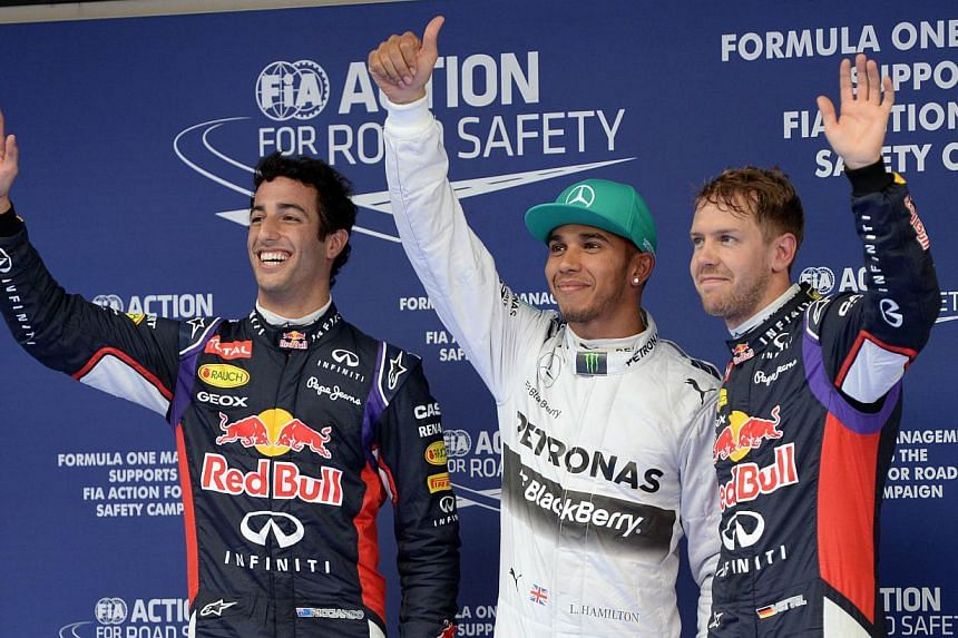 Mercedes AMG Petronas driver Lewis Hamilton (centre) of Britain celebrates after qualifying in pole position alongside second fastest Infiniti Red Bull driver Daniel Ricciardo (left) of Australia and third fastest Infiniti Red Bull driver Sebastian V