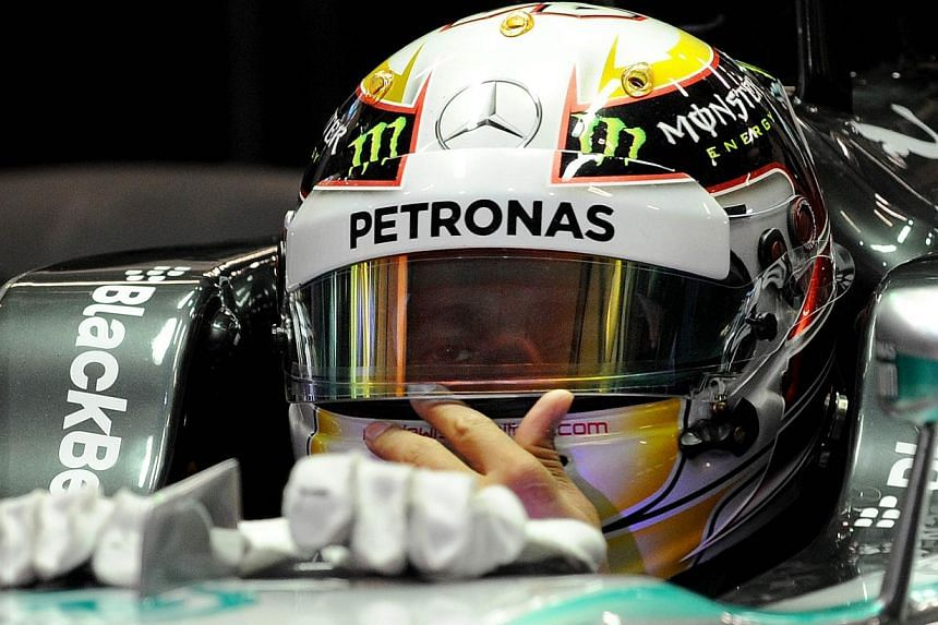 Mercedes AMG Petronas driver Lewis Hamilton of Britain sits in his car during the Formula One Chinese Grand Prix in Shanghai, on April 19, 2014. -- PHOTO: AFP