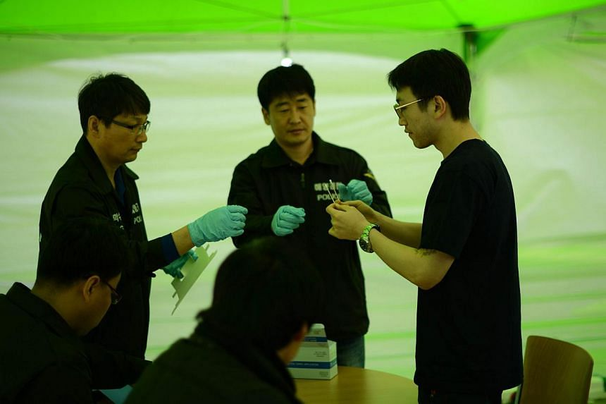A relative takes a swab from his mouth as part of a DNA test outside a gymnasium used as a gathering point for family members of missing passengers aboard the sunken South Korean ferry 'Sewol', in Jindo, on April 19, 2014. Providing a DNA sample mark