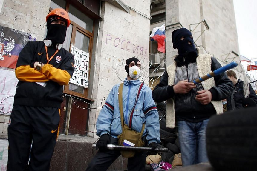 Masked pro-Russian protesters stand guard outside a regional government building in Donetsk, eastern Ukraine, on April 19, 2014. A majority of inhabitants in Ukraine's pro-Russian protest hub Donetsk do not want to join Russia but consider the govern