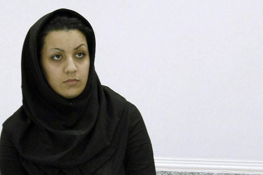 A picture taken on July 8, 2007 shows Iranian Reyhaneh Jabbari standing handcuffed at police headquarters in Teheran after she was arrested for the murder of a former intelligence official. -- FILE PHOTO: AFP