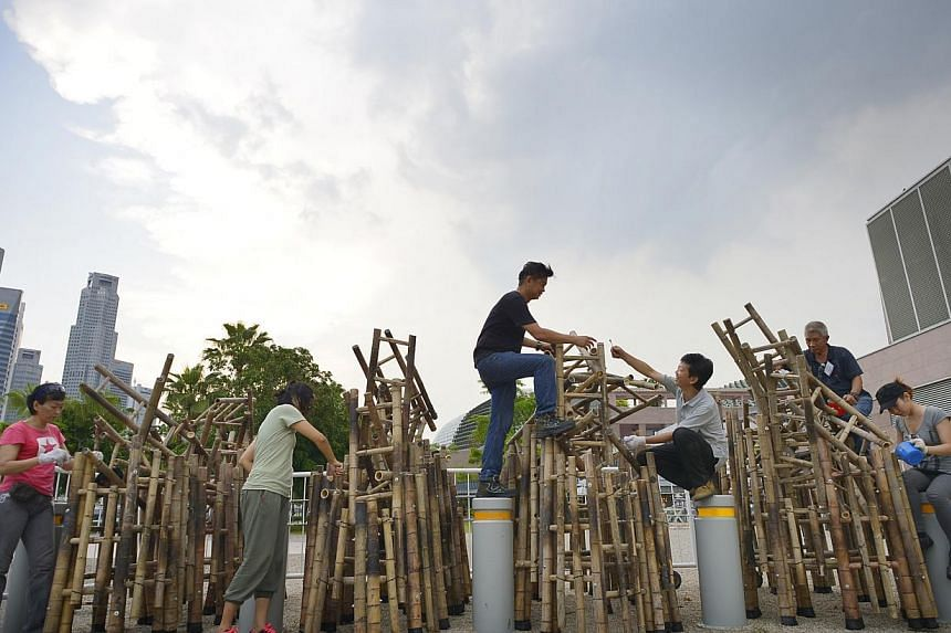 Artists (from left) Aileen Toh, Teo Huey Ling, Tay Swee Siong, Chang Wei, Chua Boon Kee and Zen Chua are among the 10 from the Sculpture Society (Singapore) who spent a week splicing, shaping and bolting 250 bamboo ladders. -- ST PHOTO: ASHLEIGH SIM