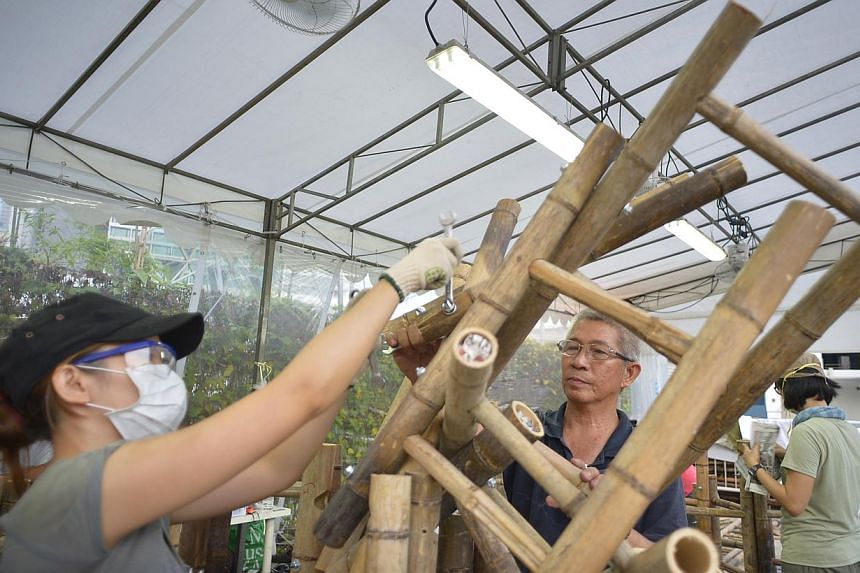 Artists Zen Chua (left) and Chua Boon Kee working on the bamboo structure. -- ST PHOTO: ASHLEIGH SIM