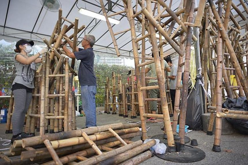 Artists Zen Chua (left) and Chua Boon Kee work on the bamboo ladders. -- ST PHOTO: ASHLEIGH SIM