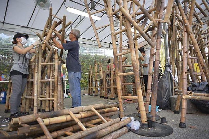Artists Zen Chua (left) and Chua Boon Kee work on the bamboo ladders. -- ST PHOTO: ASHLEIGH SIM