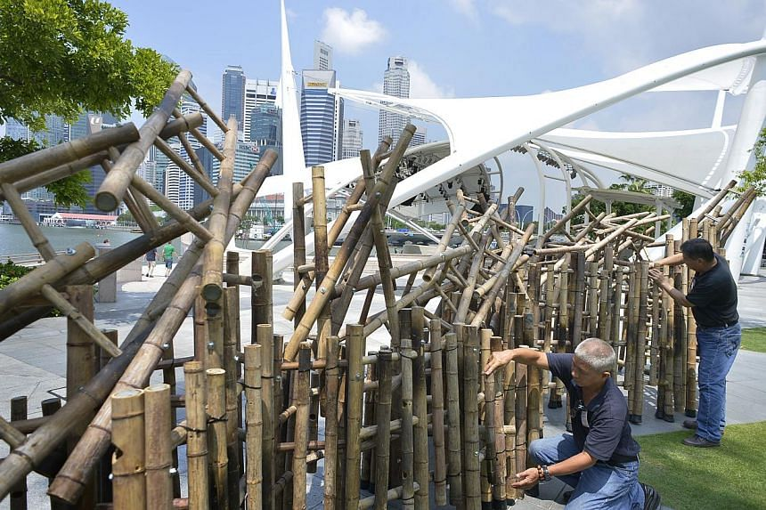 Artists Chua Boon Kee (left) and Chua Bong Siang working together on the sculpture. -- ST PHOTO: ASHLEIGH SIM
