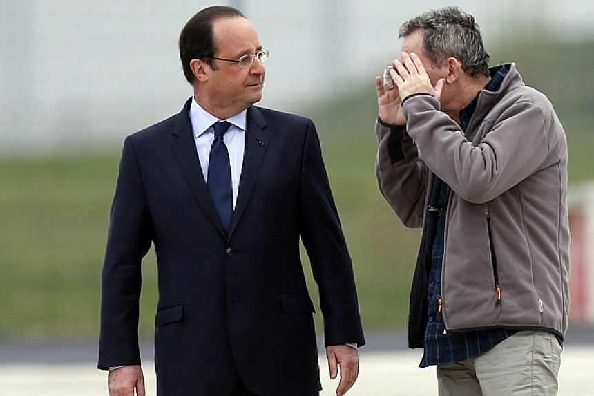 """Journalist Didier Francois (Right), former hostage, reacts as he talks to French President Francois Hollande moments after a transfer by helicopter from Evreux to the military airbase in Villacoublay, near Paris, April 20, 2014.France has """"info"""
