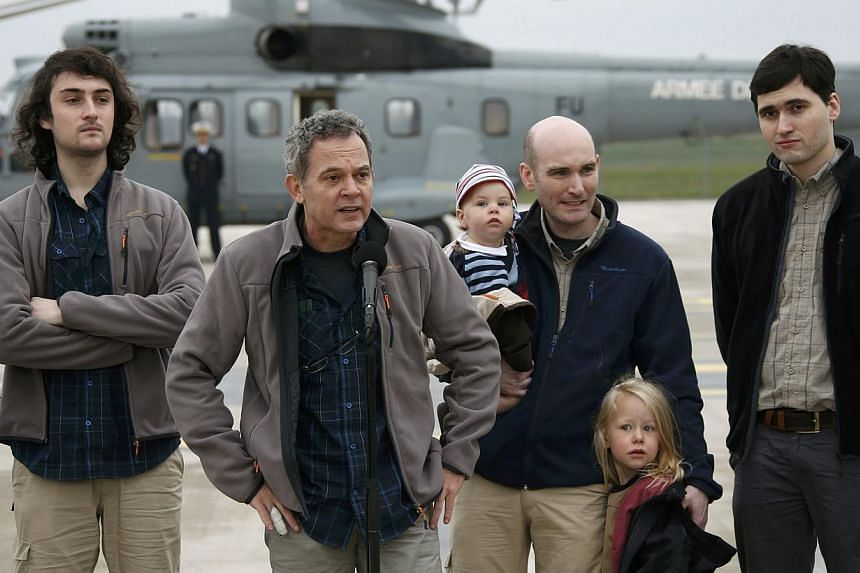 Didier Francois (Second from Left), former French hostage and journalist, speaks as he stands between Edouard Elias (Left), Nicolas Henin (Second from Right), who holds his children, and Pierre Torres (Right) moments after their arrival by helicopter
