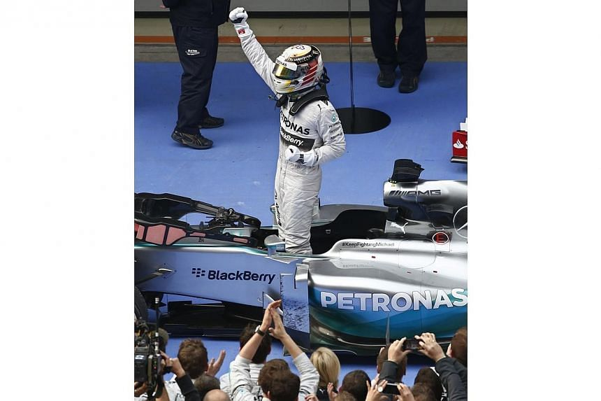 First-placed Mercedes Formula One driver Lewis Hamilton of Britain (Center) gestures as he stands in his car to celebrate his win after the Chinese F1 Grand Prix at the Shanghai International Circuit April 20, 2014. Lewis Hamilton completed a hat-tri