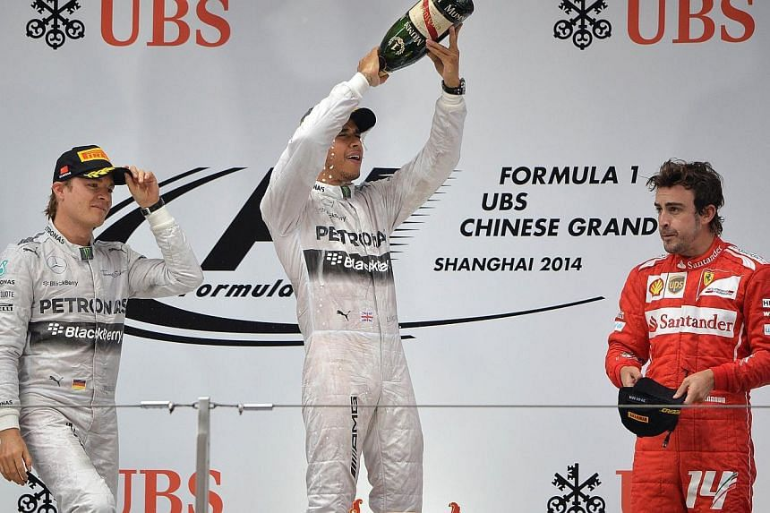 Mercedes AMG Petronas driver Lewis Hamilton of Britain (Center) celebrates besides second-placed Mercedes AMG Petronas driver Nico Rosberg of Germany (Left) and third-placed Scuderia Ferrari driver Fernando Alonso of Spain (R) on the podium after win