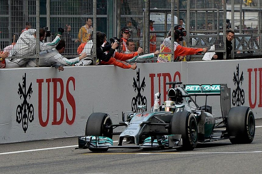 Mercedes AMG Petronas driver Lewis Hamilton of Britain celebrates on the finish line with his pit crew after winning the Formula One Chinese Grand Prix in Shanghai on April 20, 2014. Lewis Hamilton completed a hat-trick of wins by leading a Mercedes
