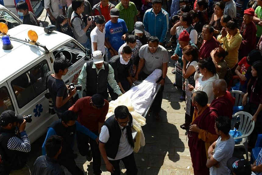 Nepalese relatives and volunteers shift the body of a Mount Everest avalanche victim after arrival at the Sherpa Monastery in Kathmandu on April 19, 2014.Bad weather suspended searches on Sunday on Mount Everest for three Nepalese sherpa guides