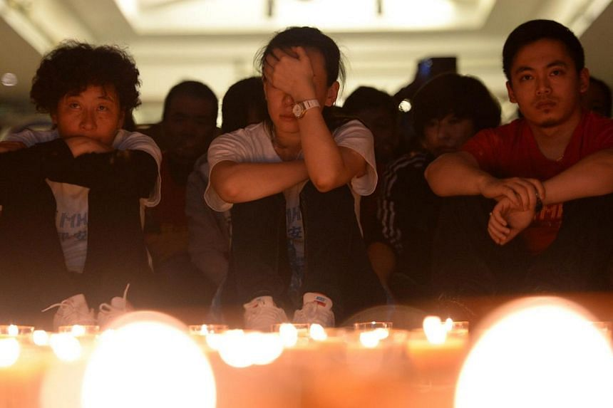 Chinese relatives of passengers on the missing Malaysia Airlines flight MH370 pray by candles at the Metro Park Hotel in Beijing on April 8, 2014.The families of the passengers and crew of flight MH370 will receive financial assistance from Mal