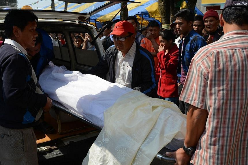 Nepalese relatives and volunteers shift the body of a Mount Everest avalanche victim after arrival at the Sherpa Monastery in Kathmandu on April 19, 2014. Nepal called off the search on Sunday for three local guides still missing after the deadl