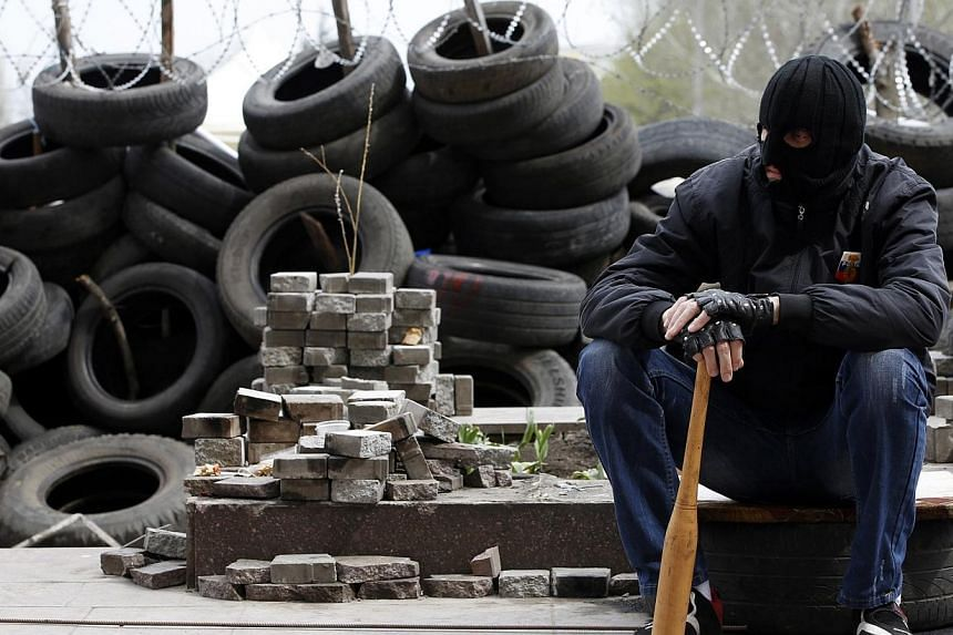 A pro-Russian protester wearing a balaclava and holding a baseball bat sits next to piles of bricks and tyres outside a regional government building in Donetsk, eastern Ukraine April 19, 2014. Three pro-Russian militants and one attacker were ki
