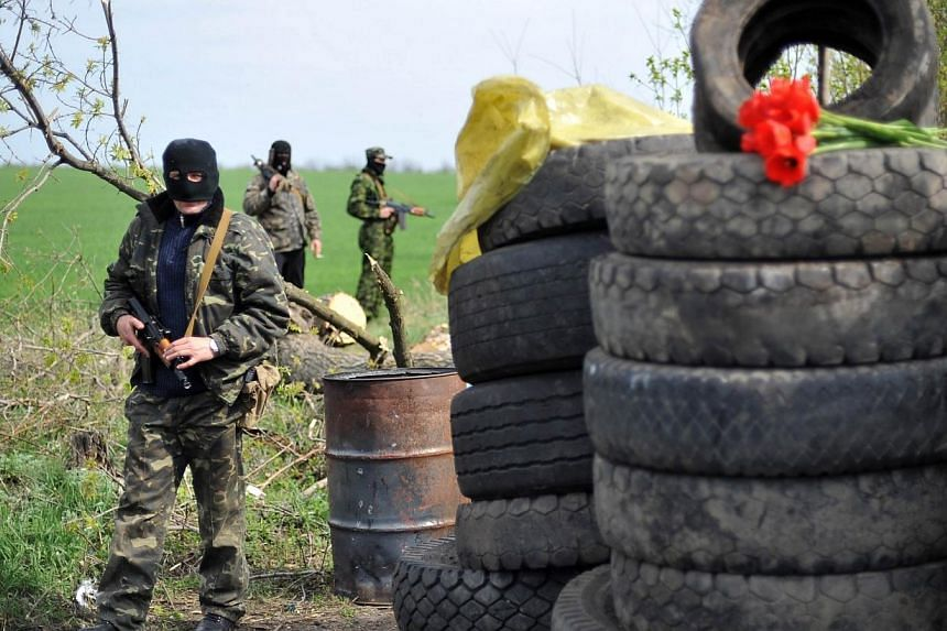 Flowers are left on tyres forming part of a roadblock at a check-point manned by armed pro-Russian militants outside the eastern Ukrainian city of Slavyansk, on April 20, 2014.Pro-Moscow rebels in the east Ukraine town of Slavyansk declared a c