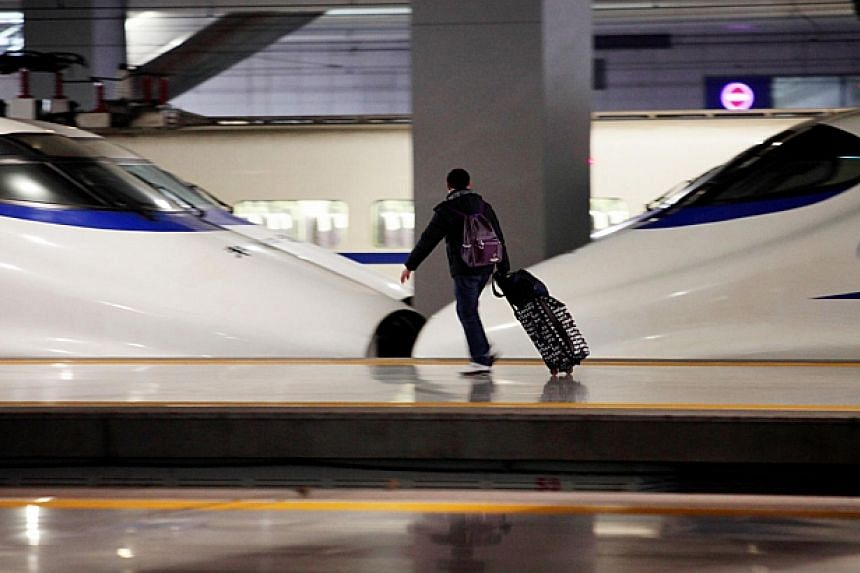 A passenger wheels his luggage past a China Railways high speed train at Hongqiao Railway Station in Shanghai, China on Friday, Feb. 8, 2013. -- FILE PHOTO: BLOOMBERG