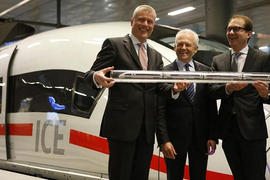 Jochen Eickholt, CEO Siemens AG Rail Systems, CEO of the German railway firm Deutsche Bahn Ruediger Grube and German Transport Minister Alexander Dobrindt (left-right) pose for the media in front of a Deutsche Bahn ICE 3 high speed train during an ha