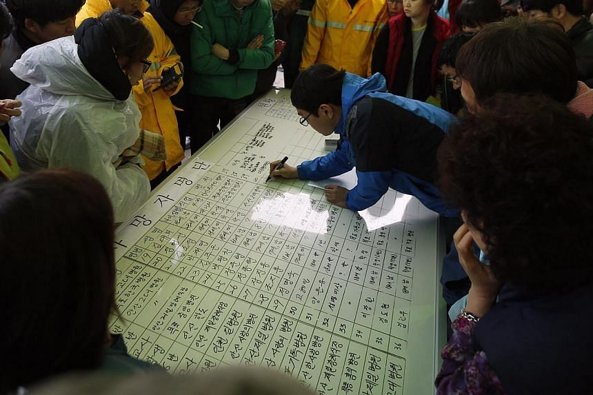 Family members of missing passengers who were on the South Korean ferry Sewol looking at the list of fatalities in Jindo on April 20, 2014. -- PHOTO: REUTERS