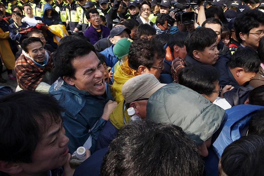 Family members of passengers missing after the ferry Sewol capsized clash with police in Jindo during a protest calling for a meeting with President Park Geun-hye and demanding the search and rescue operation be sped up on April 20, 2014. -- PHOTO: R