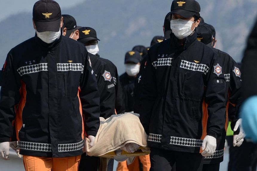 Rescue workers carrying the body of a victim recovered by research and rescue teams from the sunken South Korean ferry Sewol upon arrival at Jindo harbour on April 20, 2014. -- PHOTO: AFP
