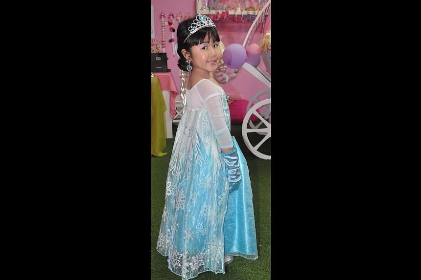 Frozen-themed birthdays for Jerraine Tan (above), five, in the Queen Elsa gown, as well as for Rachel Ling, five, and sister Emma, three, dressed as Elsa and Anna, the queen's younger sister in the movie. -- PHOTO: JASLYN SIM