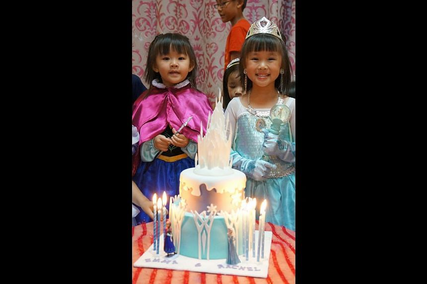 Frozen-themed birthdays for Jerraine Tan, five, in the Queen Elsa gown, as well as for Rachel Ling (above right), five, and sister Emma (above left), three, dressed as Elsa and Anna, the queen's younger sister in the movie. -- PHOTO: LISA LING