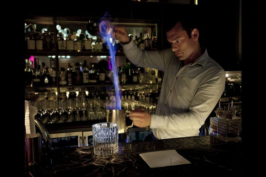 """This warm cocktail is prepared in front of you, with the bartender pouring the mixture """"teh-tarik""""- style (above) to reduce the alcohol content to 20 per cent before it is stirred with a fresh rosemary sprig. -- PHOTO: INTERCONTINENTAL AMSTEL AMS"""