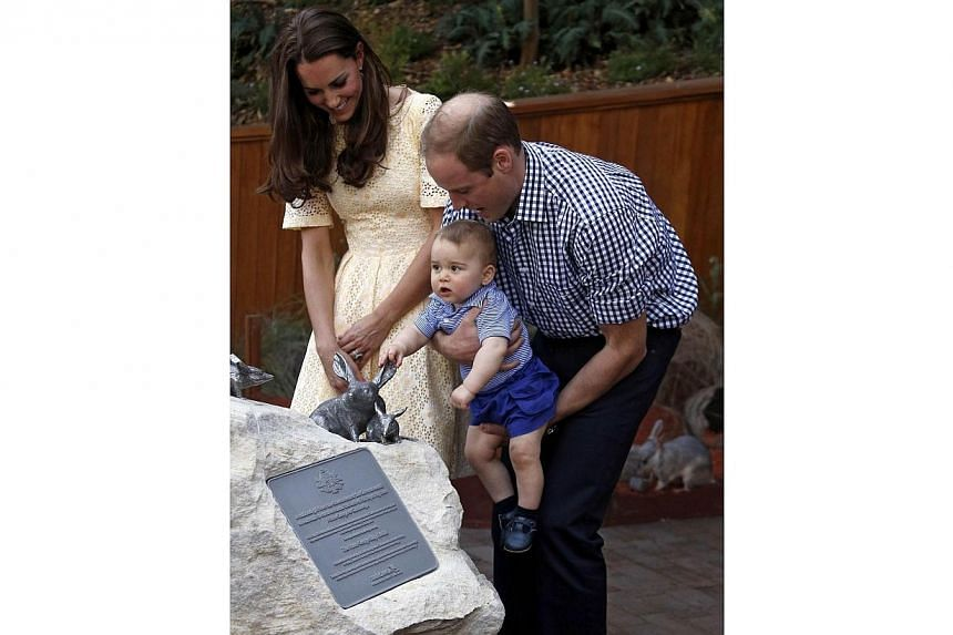 Catherine, the Duchess of Cambridge (left), and her husband, Britain's Prince William, watch as their son Prince George reacts after they unveiled a plaque to commemorate their visit to the enclosure for the Australian animal called a bilby during a
