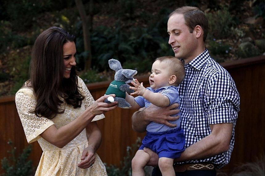 Catherine, the Duchess of Cambridge (left), and her husband, Britain's Prince William (right), react as their son Prince George grabs at a toy of an Australian animal called a bilby during a visit to Sydney's Taronga Zoo on April 20, 2014. -- PHOTO: