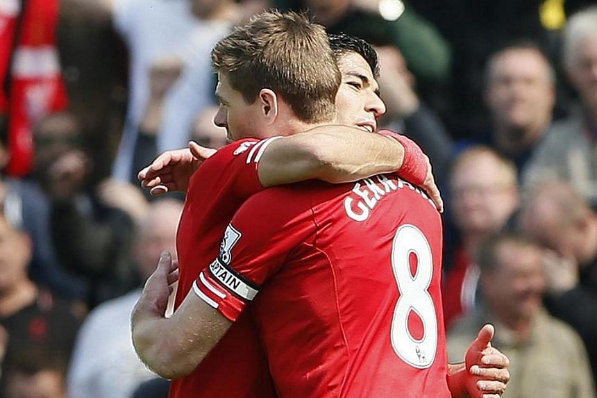 Liverpool captain Steven Gerrard (right) hugs teammate Luis Suarez after winning their English Premier League soccer match against Norwich City at Carrow Road in Norwich on April 20, 2014. Liverpool took a giant step towards their first top-flight le