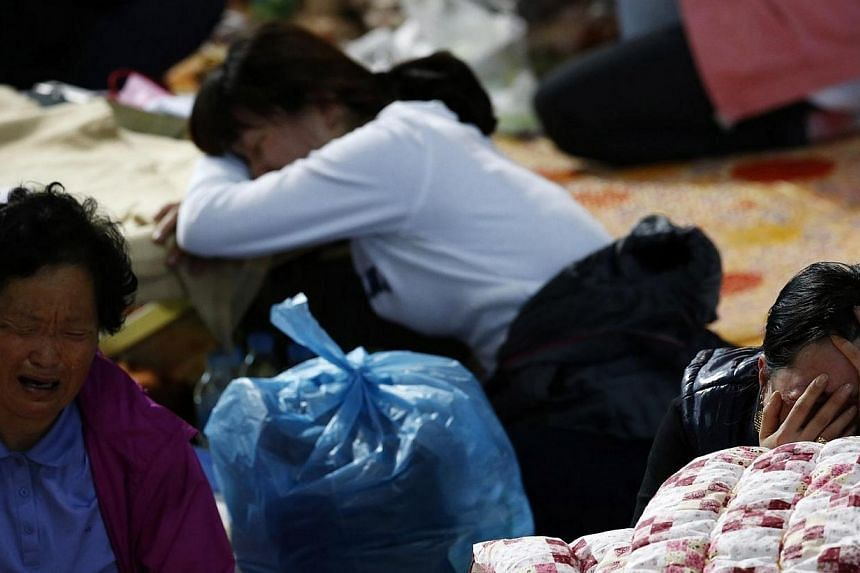 Family members of missing passengers onboard the South Korean ferry Sewol which capsized on Wednesday, April 16, 2014, cry as they check the newly announced list of dead at a gym in Jindo on April 20, 2014. Kim Ha Nna no longer sleeps or eats and is