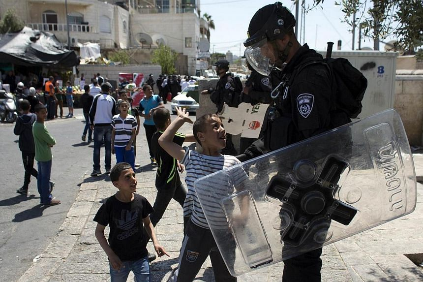 A Palestinian child gestures towards a member of the Israeli security forces as he stands guard in the east Jerusalem neighbourhood of Ras al-Amud on April 18, 2014. Israeli police arrested 16 Palestinians on Sunday, April 20, 2014, as they clashed w