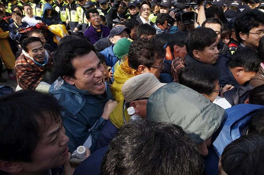 Family members of passengers missing after the ferry Sewol capsized clash with police in Jindo during a protest calling for a meeting with President Park Geun-hye and demanding the search and rescue operation be speeded up on April 20, 2014. South Ko