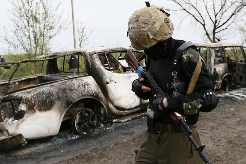 A Pro-Russian militant walks past burnt cars near a checkpoint that was the scene of a gunfight overnight near the city of Slaviansk on April 20, 2014.At least two people were killed in a gunfight early on Sunday, April 20, 2014,near a Uk