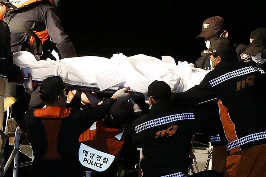 A covered body of a missing passenger of the sunken South Korean ferry Sewol is carried by rescue workers from a coastguard ship to the landing pier at a port, where family members of the missing passengers are gathered, in Jindo on April 19, 2014. -