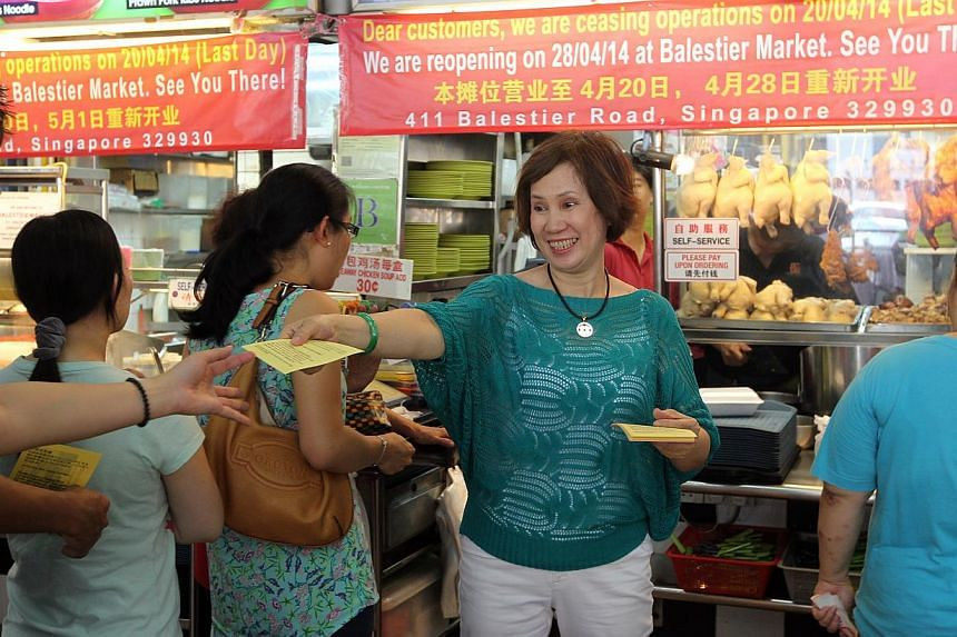 Madam Yong Fong (facing camera), owner of Bugis Street Chuen Chuen Chicken Rice handing out flyers to Longhouse customers informing them of the stall's new location in Balestier Road. The 14-year-old Longhouse food centre in Upper Thomson Road closed