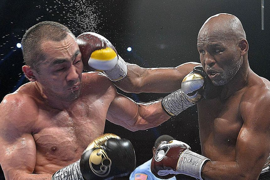 Bernard Hopkins (right) of the United States exchanges blows with Beibut Shumenov (left) of the United States during their WBA & IBA Light-heavyweight title fight at the DC Armory in Washington on April 19, 2014. -- PHOTO: AFP
