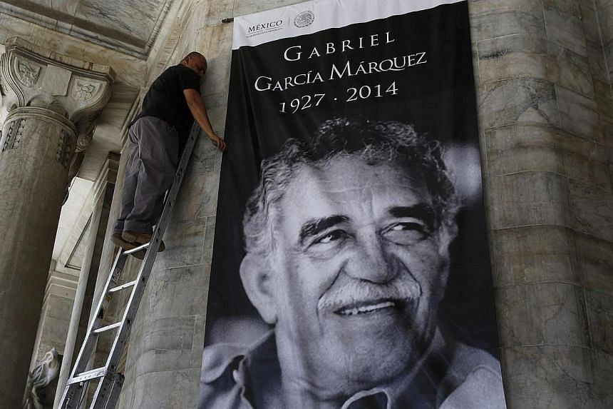 A worker arranges a banner with the picture of late Nobel Prize laureate Gabriel Garcia Marquez at the Bellas Artes palace in Mexico City on April 20, 2014. The Colombian writer, who died on April 17 aged 87, made magic realism famous with his novels