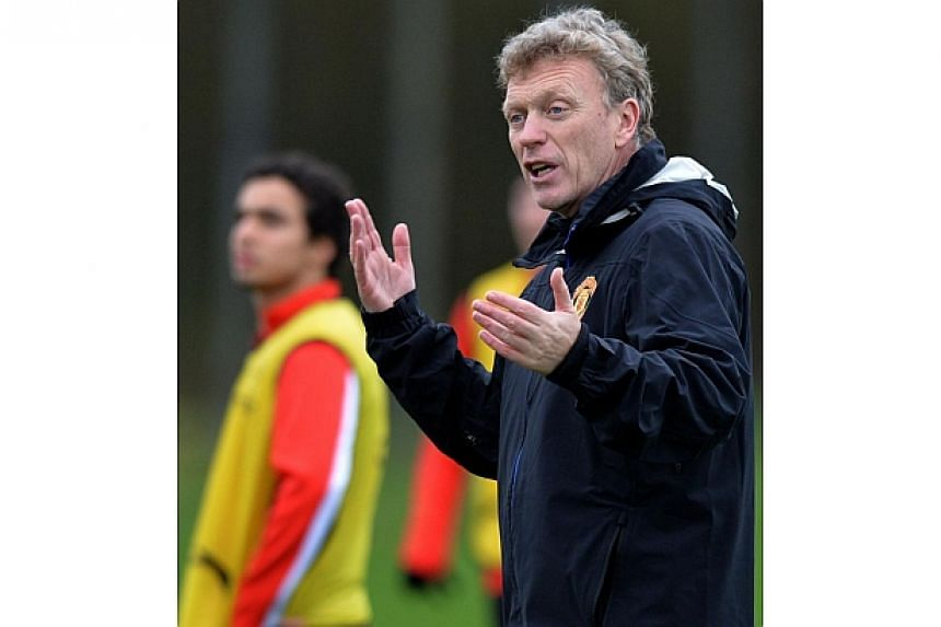 Manchester United's Scottish manager David Moyes (right) gestures during a training session at their Carrington complex in Manchester, north west England, on Feb 24, 2014, ahead of the UEFA Champions League football match between Olympiakos and Manch