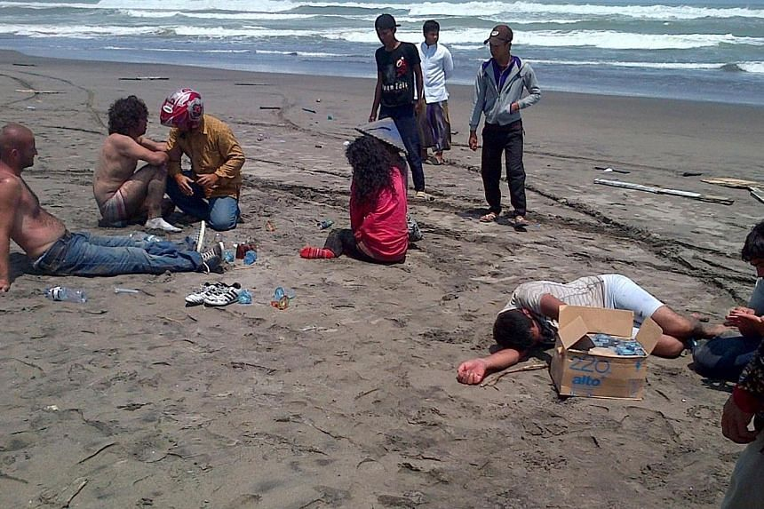 Residents helping a group of asylum-seeker survivors on the beach after being rescued by locals in the coastal village of Cianjur, located in Indonesia's western Java island on Sep 27, 2013. Jakarta called on governments on Monday, April 21, 2014, to