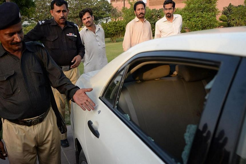 A Pakistani policeman points to a bullet hole ront on a car door following an attack on prominent Pakistani journalist Hamid Mir in Karachi on April 19, 2014. A leading Pakistani journalist and TV anchor who was shot three times in an attack in