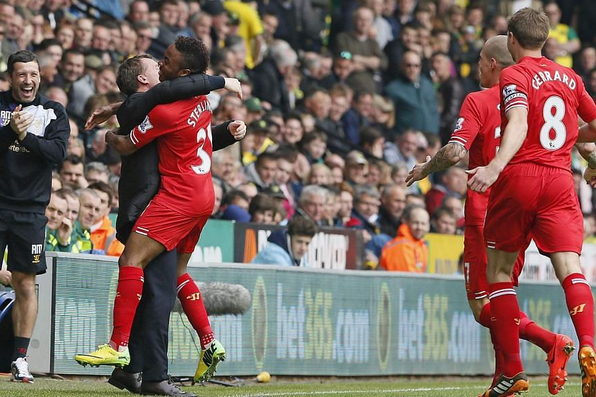 Liverpool's Raheem Sterling (centre) celebrates his goal against Norwich City with manager Brendan Rodgers (second from left) during their English Premier League soccer match at Carrow Road in Norwich, on April 20, 2014. Liverpool manager Brendan Rod